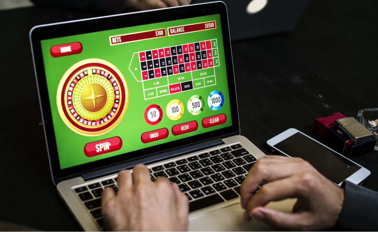 Close up of man playing online casino games on a laptop