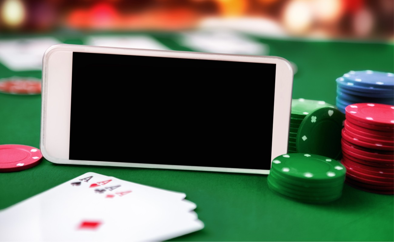 Smartphone with chip cards and four aces illustrating online poker.