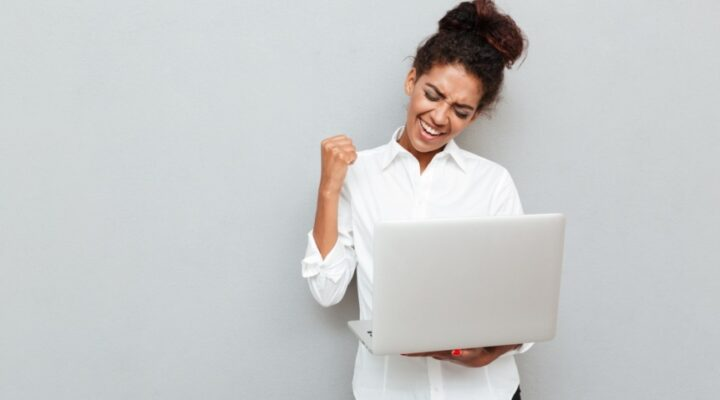 Photo of a cheerful businesswoman standing against a grey wall, holding a laptop, and celebrating a win.
