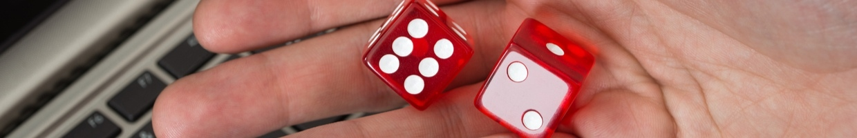 Hand holding two red dice above keyboard