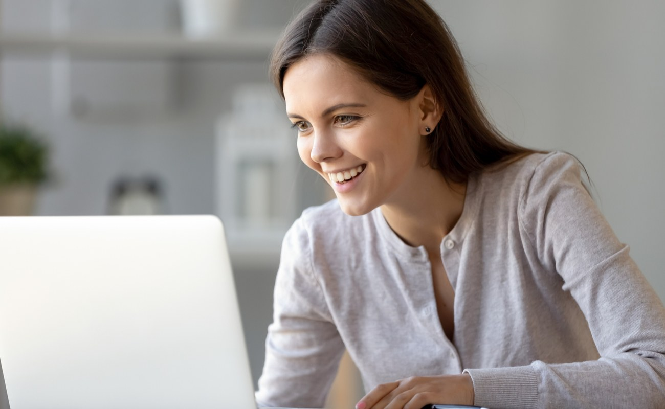 A young woman happily learns how to play online poker.