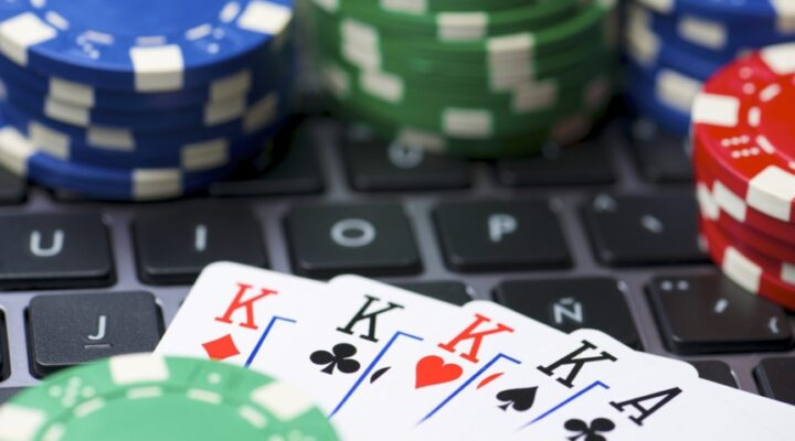 A poker hand lies across a laptop keyboard surrounded by casino chips.