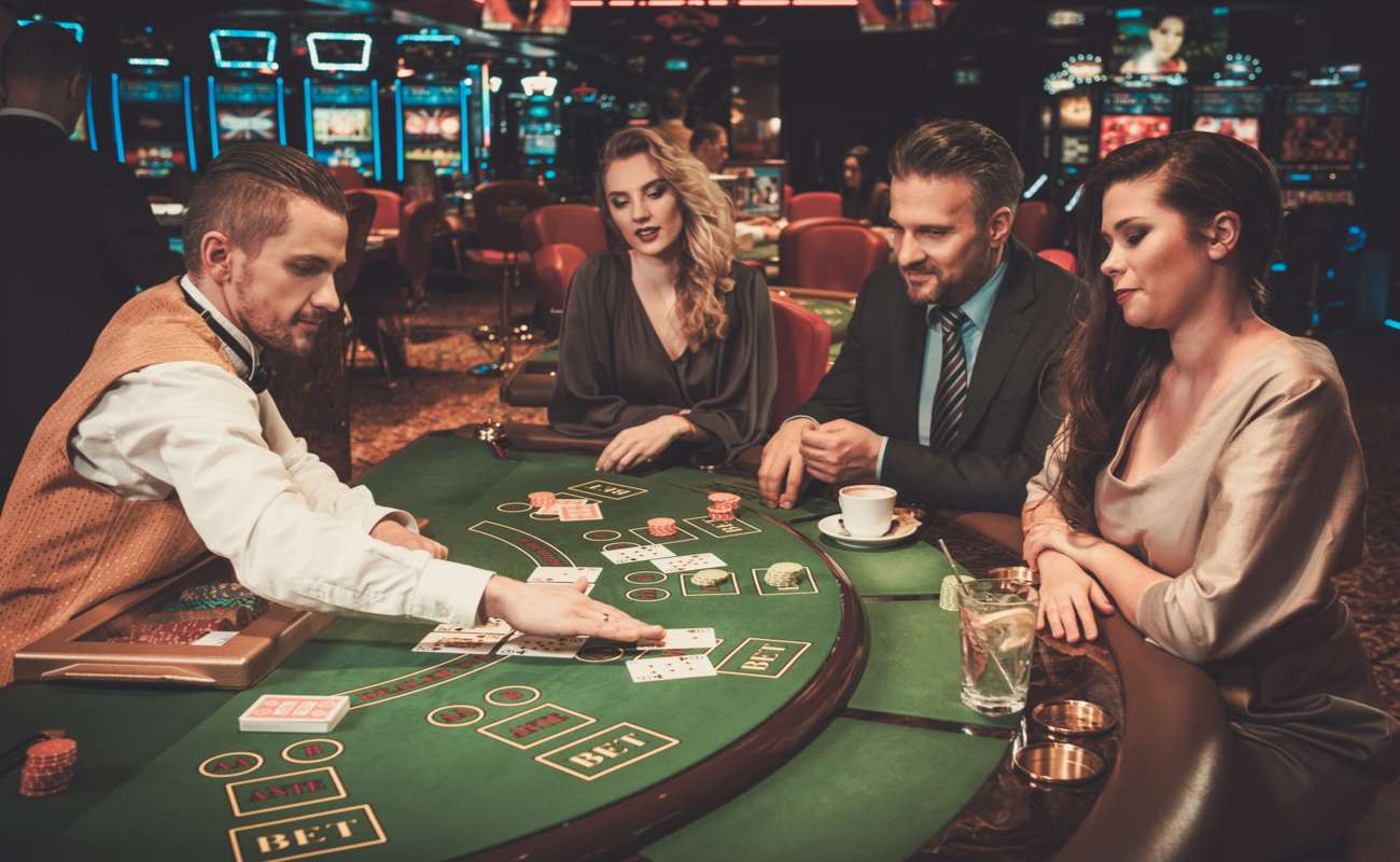 Two well-dressed women and a man playing cards at a table with a dealer in a casino.