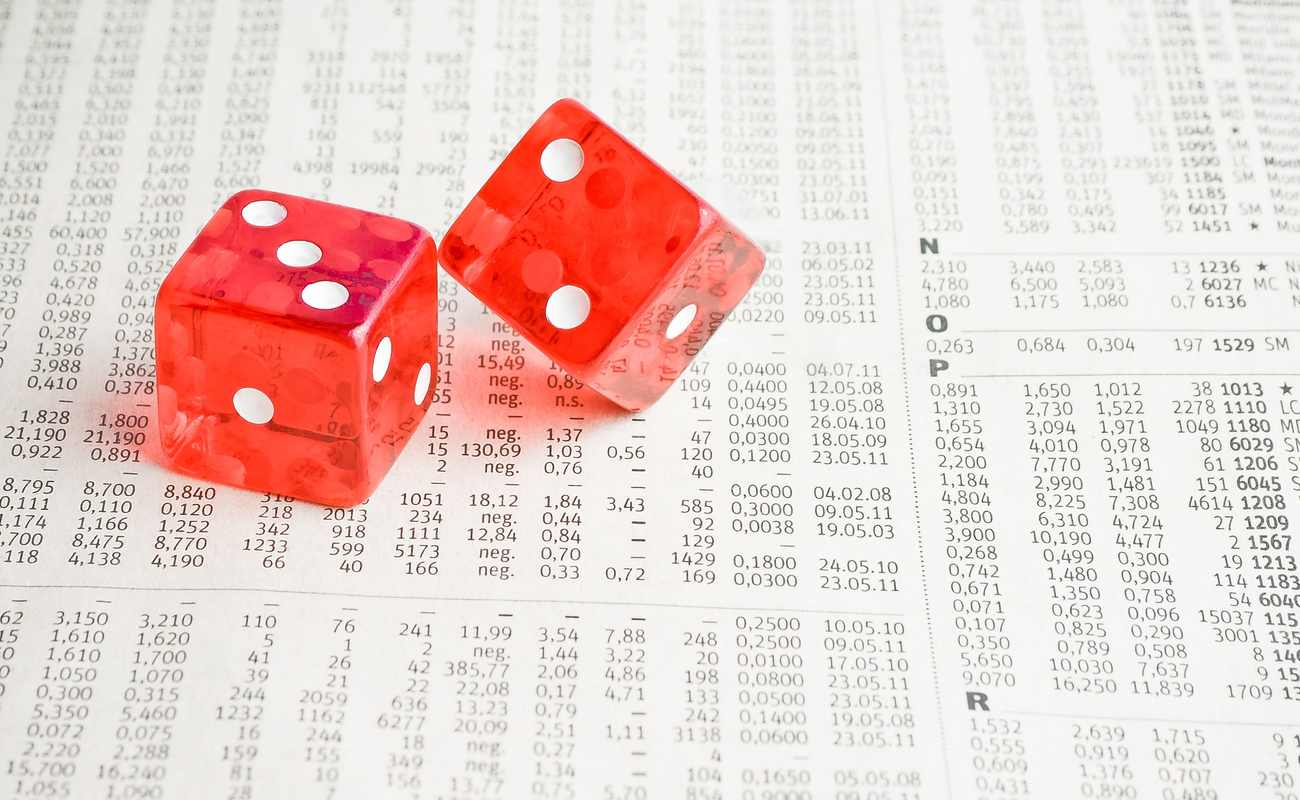 A pair of red dice sit on top of a printout with financial values on it.