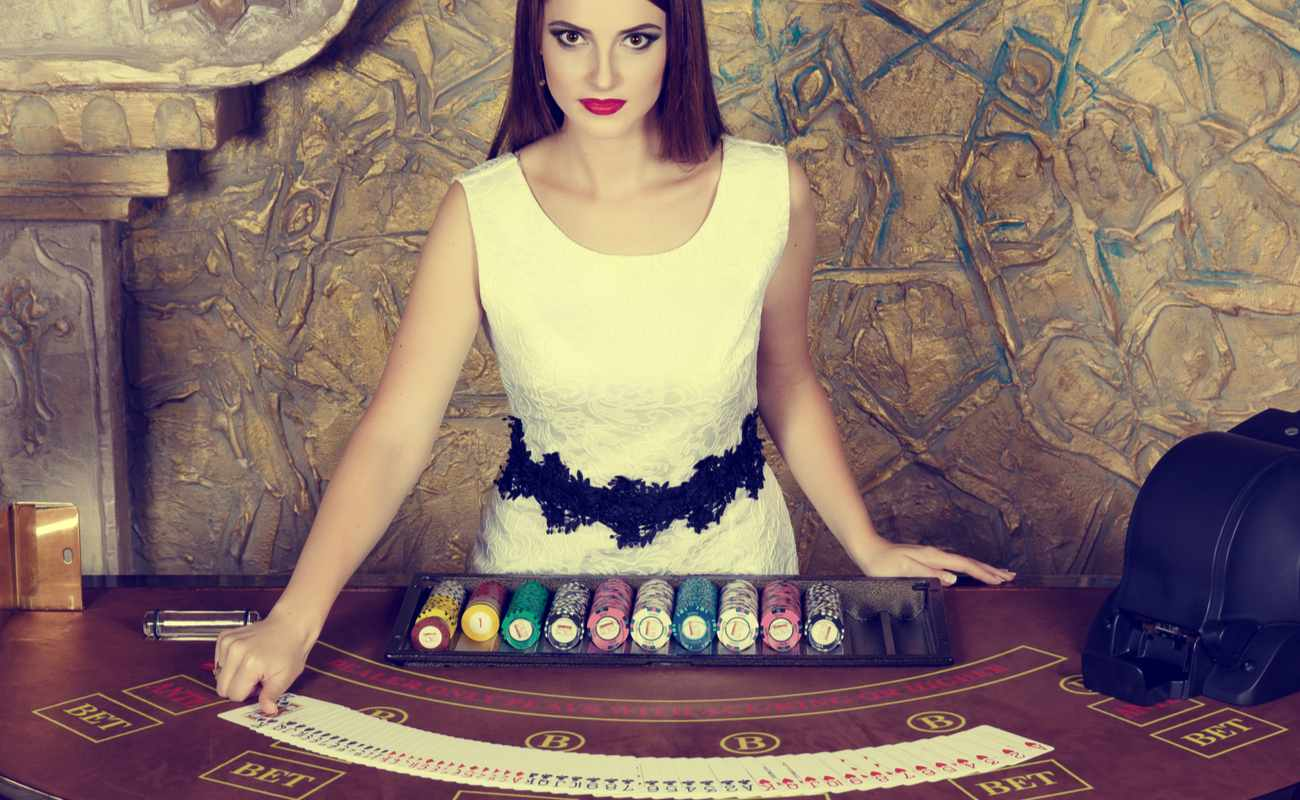 A female dealer stands at a decorated casino table with playing cards and casino chips.
