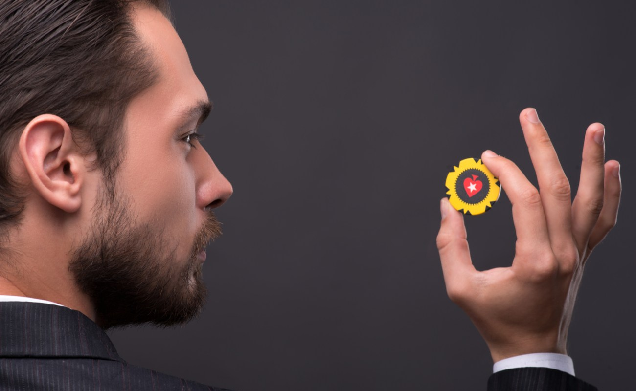 A bearded man in a suit holding up a yellow poker chip against a dark gray background.