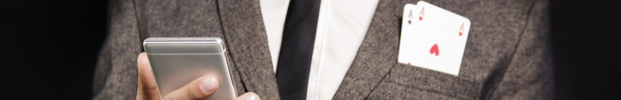 Man in a suit with aces in his front pocket holding a mobile device.