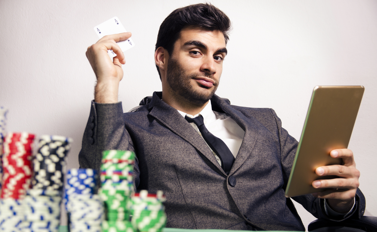 Elegant man in a suit holding the ace of spades and a tablet with stacks of poker chips in the foreground.
