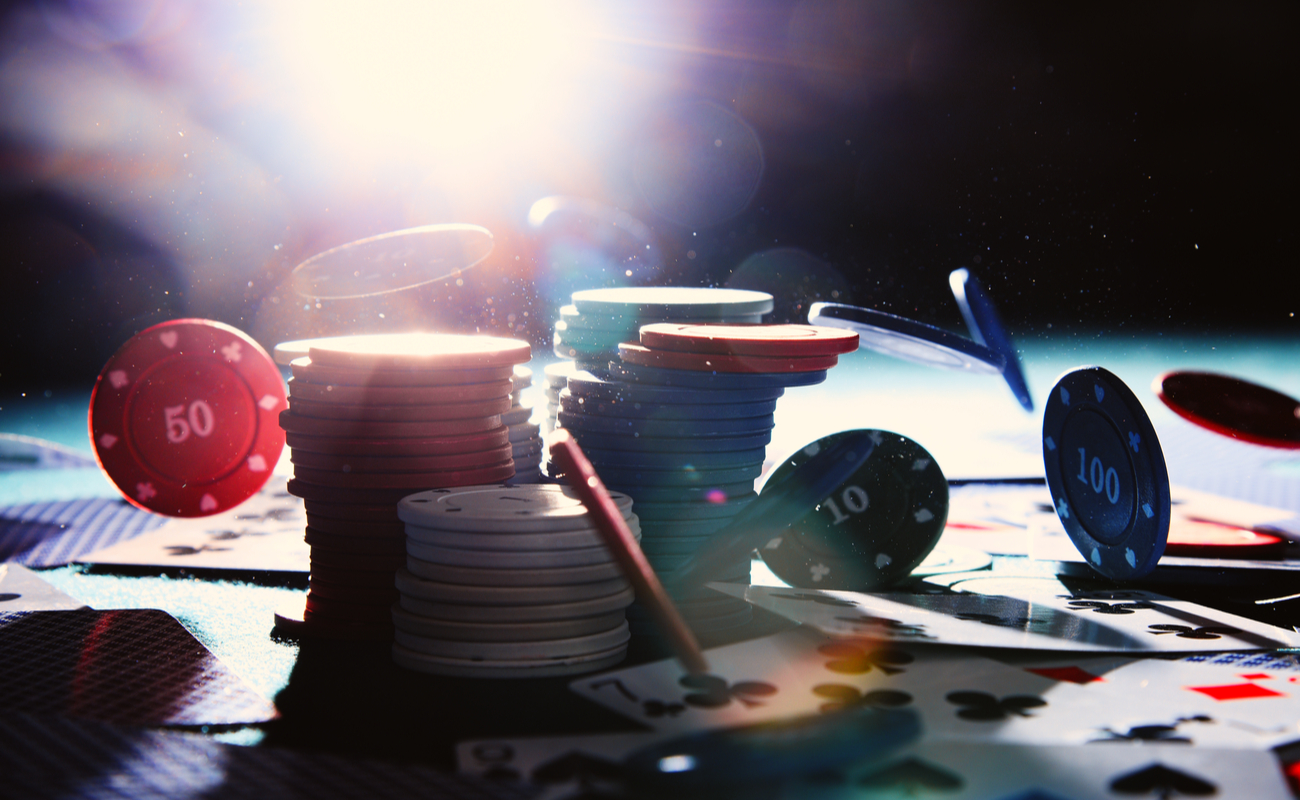 Digital render of stacks of poker chips with playing cards scattered on a casino table.