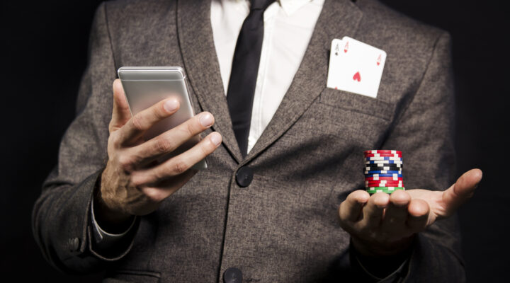 Man earing a gray suit holding a phone in one hand and poker chips in the other