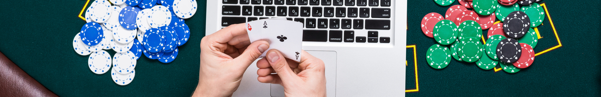 Man's hands holding a pair of aces over a laptop on a green casino table, with piles of casino chips.