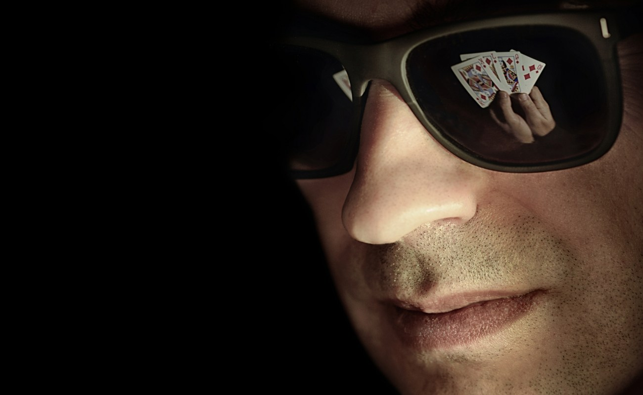 Man with sunglasses with the lenses reflecting playing cards he is holding in his hands.