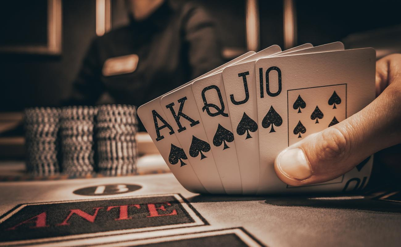 A royal flush of spades on a casino table with poker chips and the dealer in the background.
