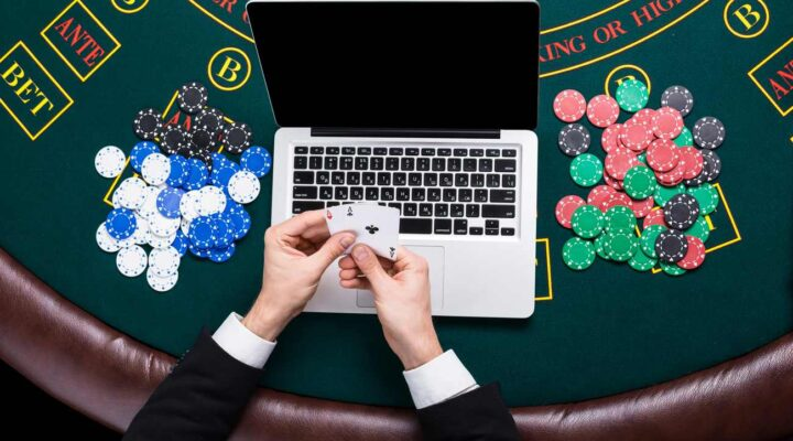Hands holding cards in front of laptop on casino table