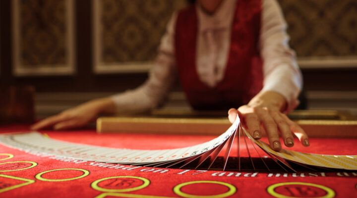 Croupier shuffling cards on a red felt table