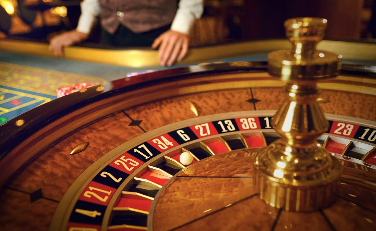 Dealer standing next to a roulette table and wheel with the ball landed on 34