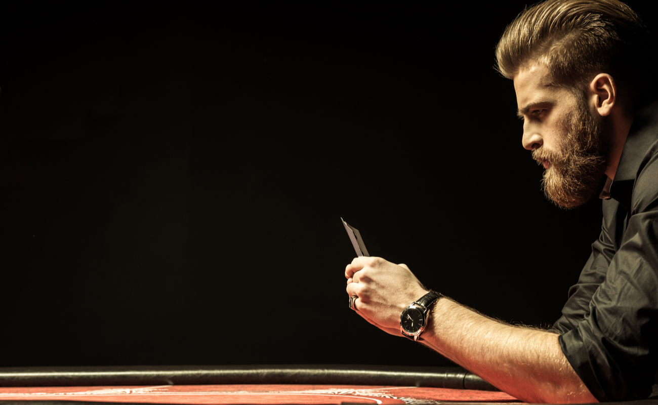 A man sitting at a poker table looking at his cards.