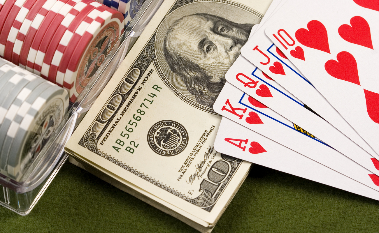 A wad of one-hundred-dollar notes, surrounded by poker chips and playing cards.