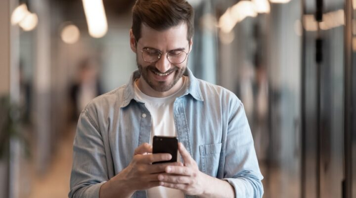 Young male employee in glasses smiling while looking at cellphone.