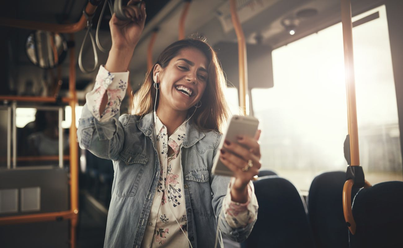 Young woman wearing earphones laughing at a text message on her cellphone while riding on a bus.