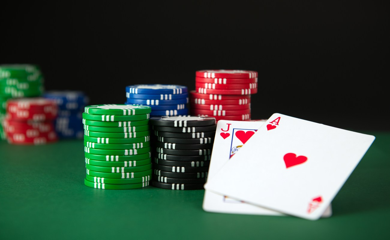 A jack and ace of hearts sit next to stacks of casino chips on a green table.