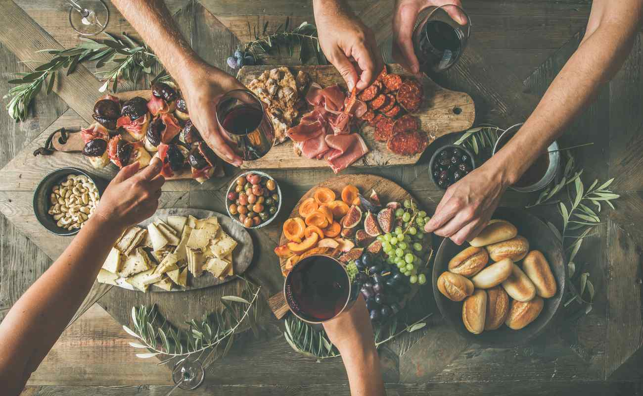 People help themselves to various snacks from a platter that includes fruit, cold meats, and cheese.