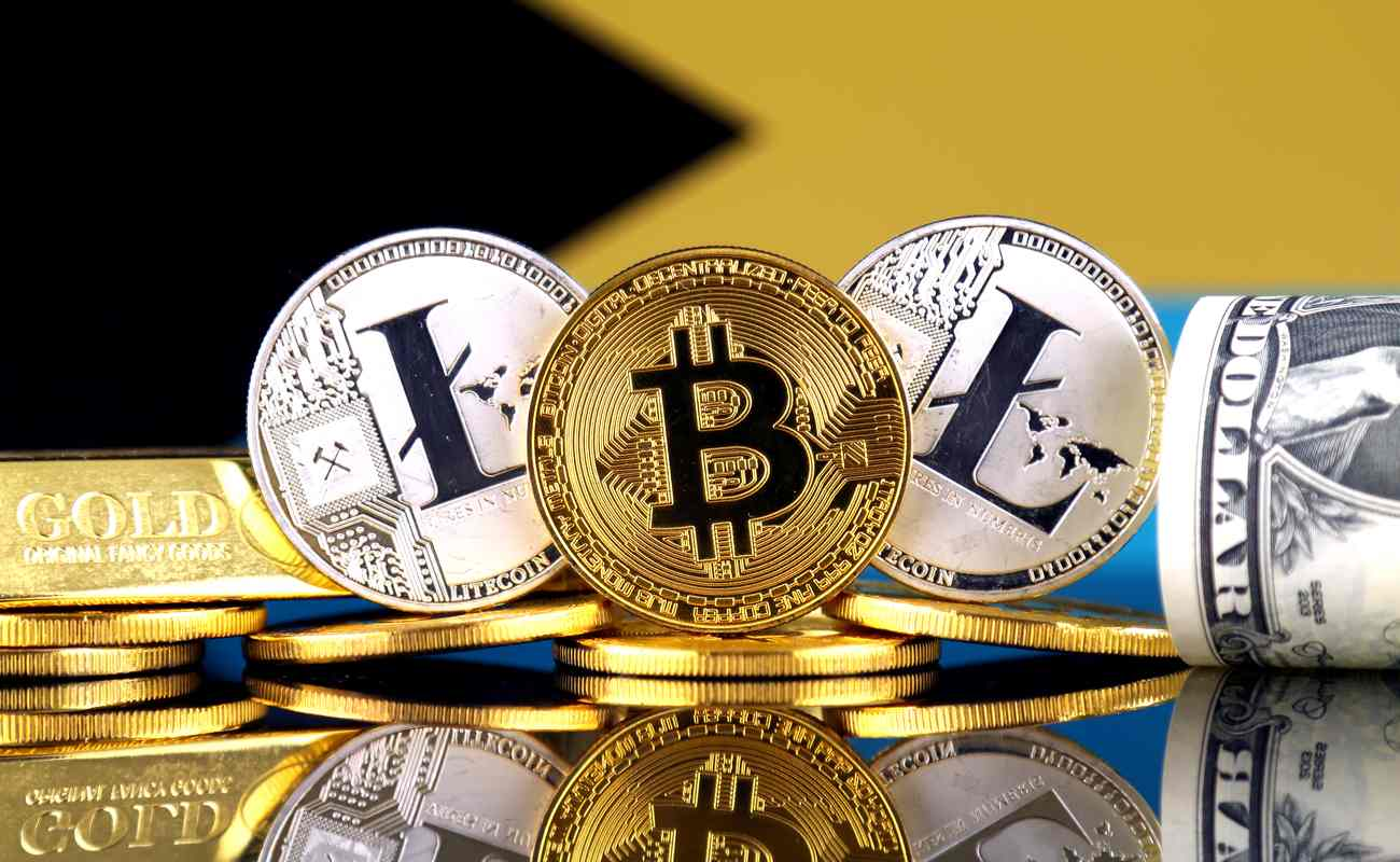 Three coins representing cryptocurrency are visible next to a gold bar and a roll of US dollars.