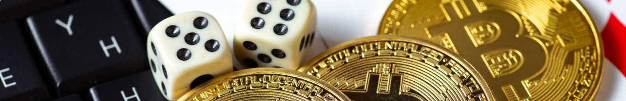 three coins representing cryptocurrency sit on a keyboard next to a pair of dice and some playing cards.