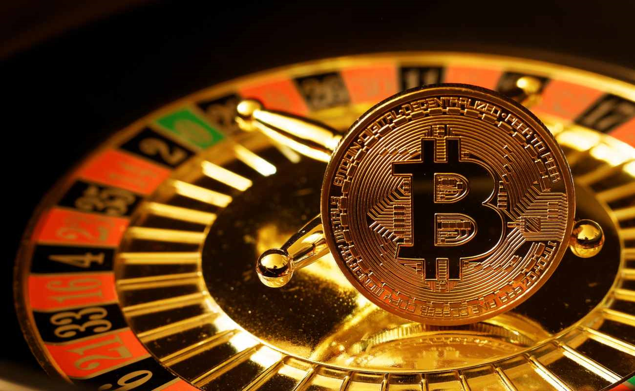 A coin with the Bitcoin symbol on it rests on a roulette wheel.