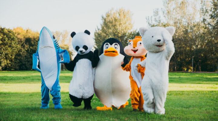 A shark, panda, penguin, chipmunk, and bear mascot walking together.