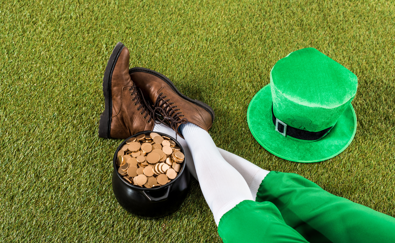 A leprechaun sitting on the grass next to a pot of gold with a top hat next to him.