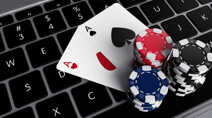 A keyboard with playing cards and casino chips.