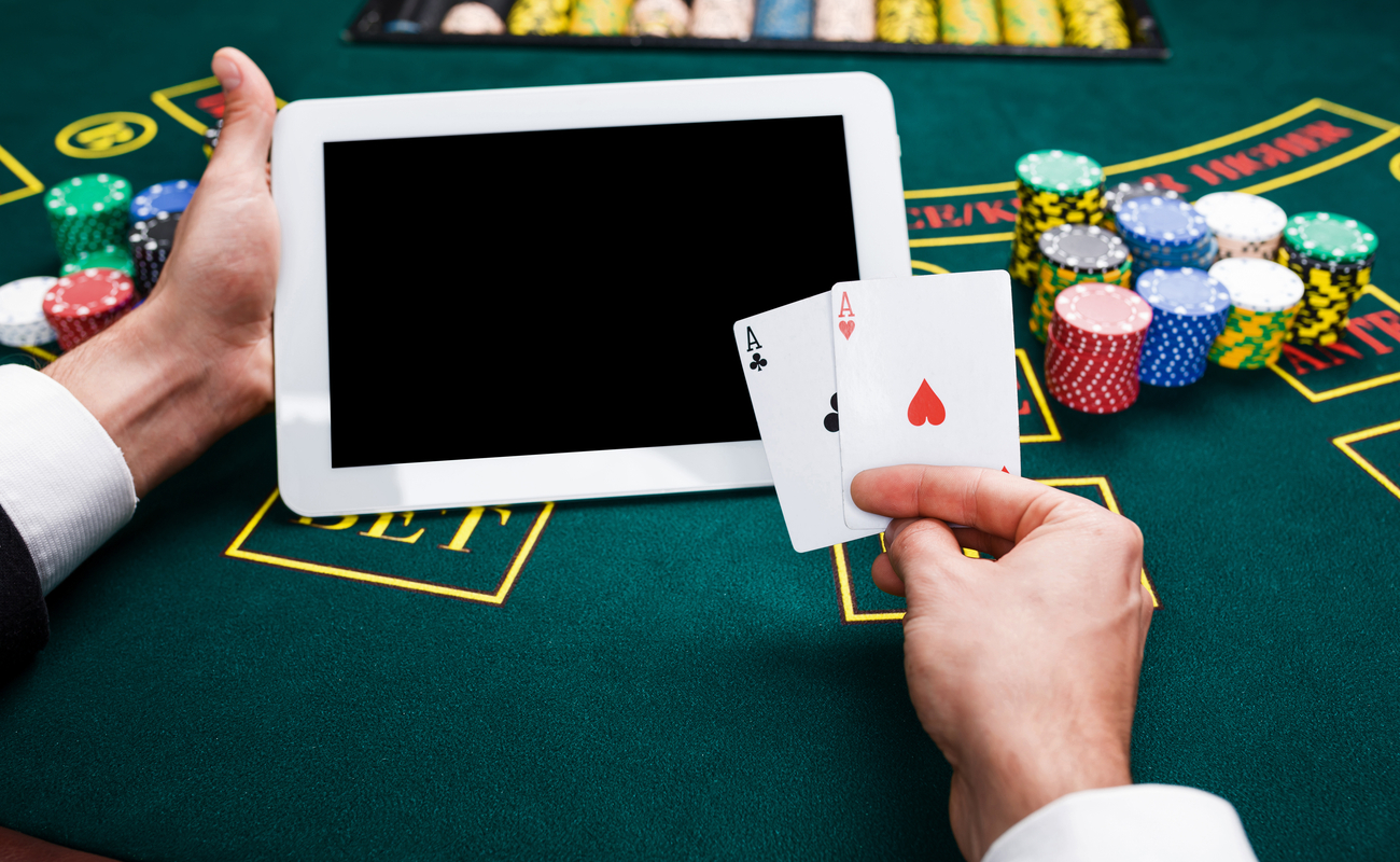 A man plays blackjack at a casino table with a tablet, a pair of aces, and casino chips.