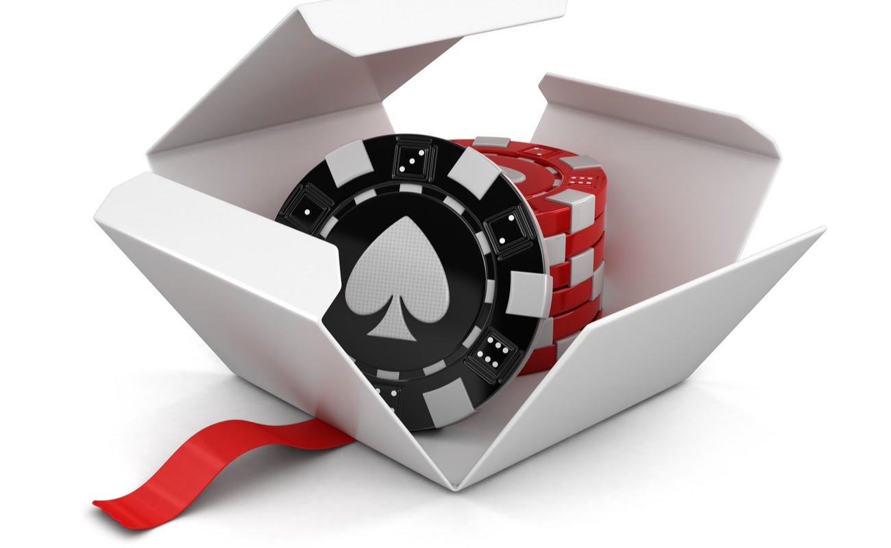 Red and black casino chips in an open white gift box with red ribbon.