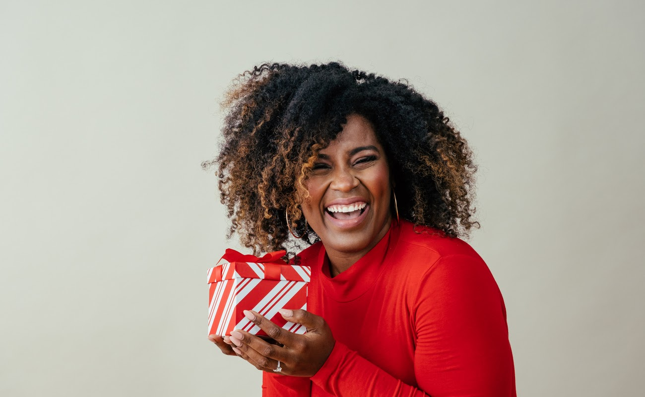 A happy woman in red receives a red and white gift box.
