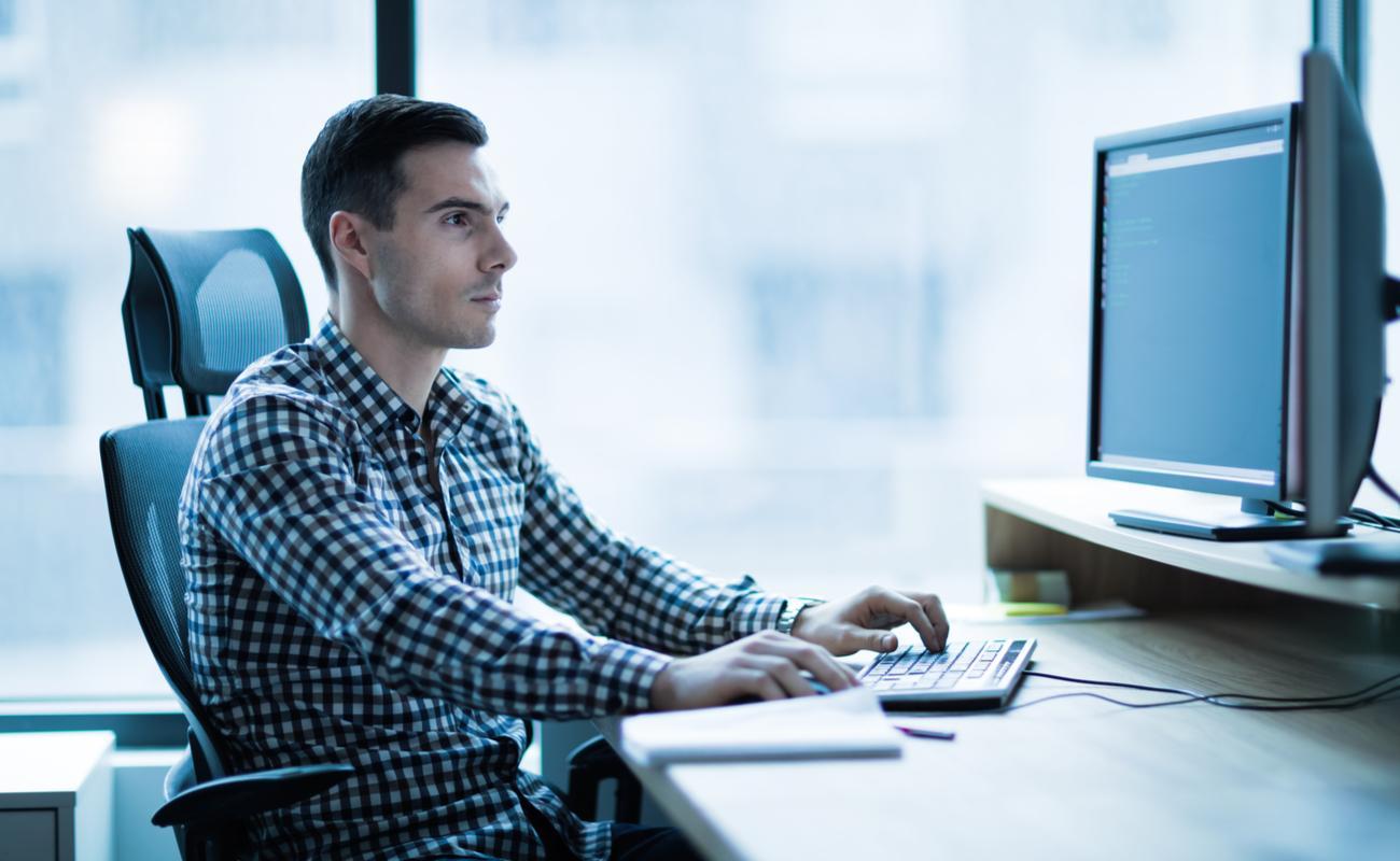 A man works on his dual-screen desktop PC.