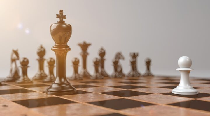 Close-up of a chessboard where a white pawn faces a black king.