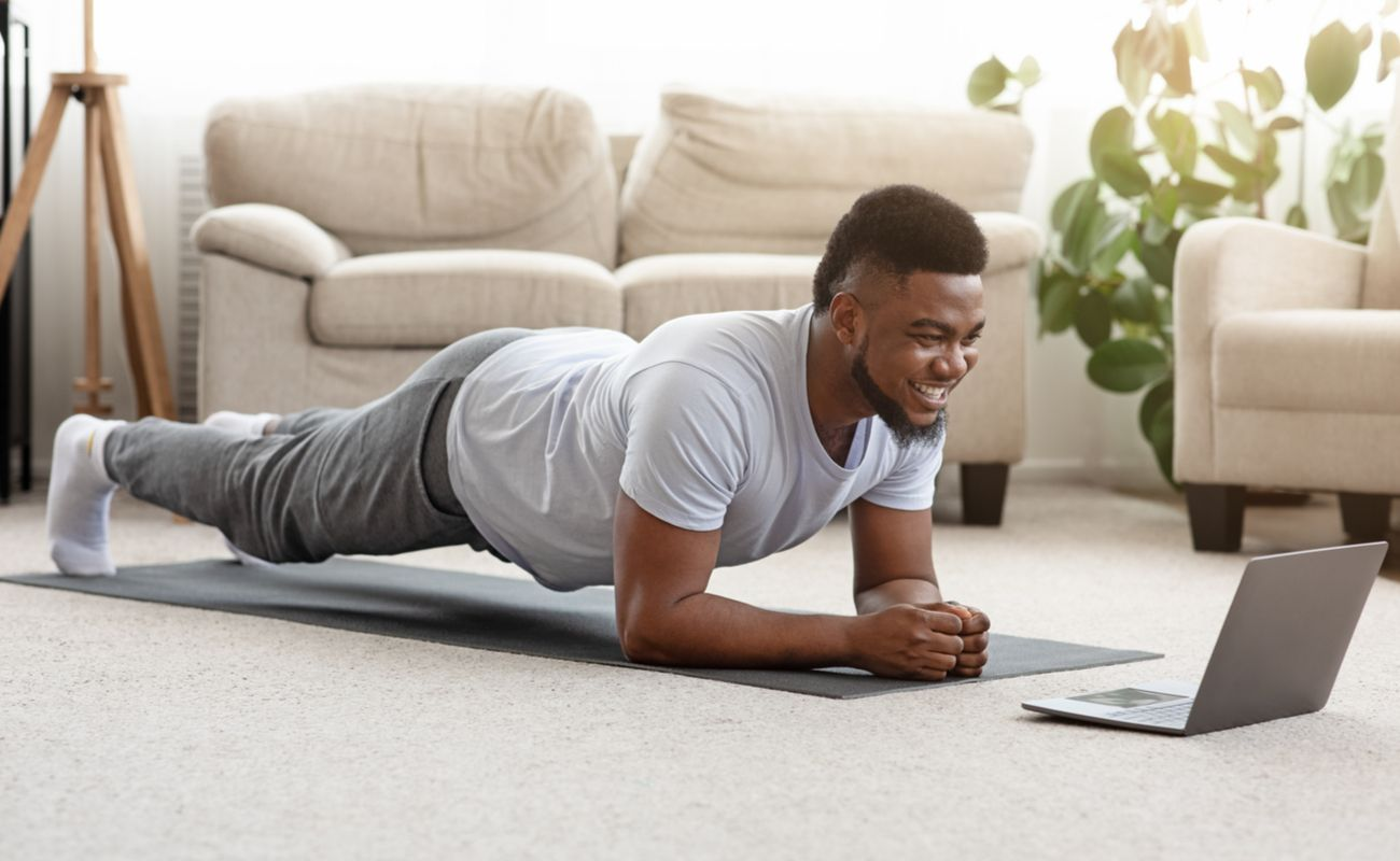 A man doing a plank exercise in front of his laptop.