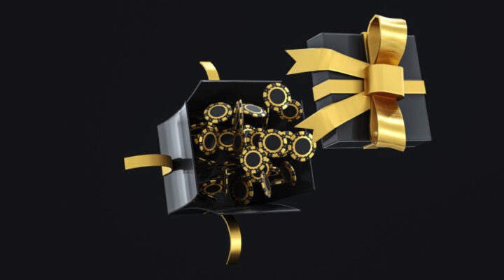 Black and gold casino chips bursting out of a black gift box with gold ribbon against a black background.