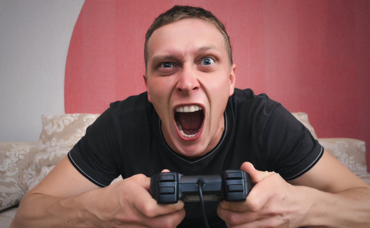 A man sitting on a couch with a controller in his hand screams at the TV.