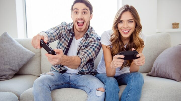 A couple sit together on the couch and play games.