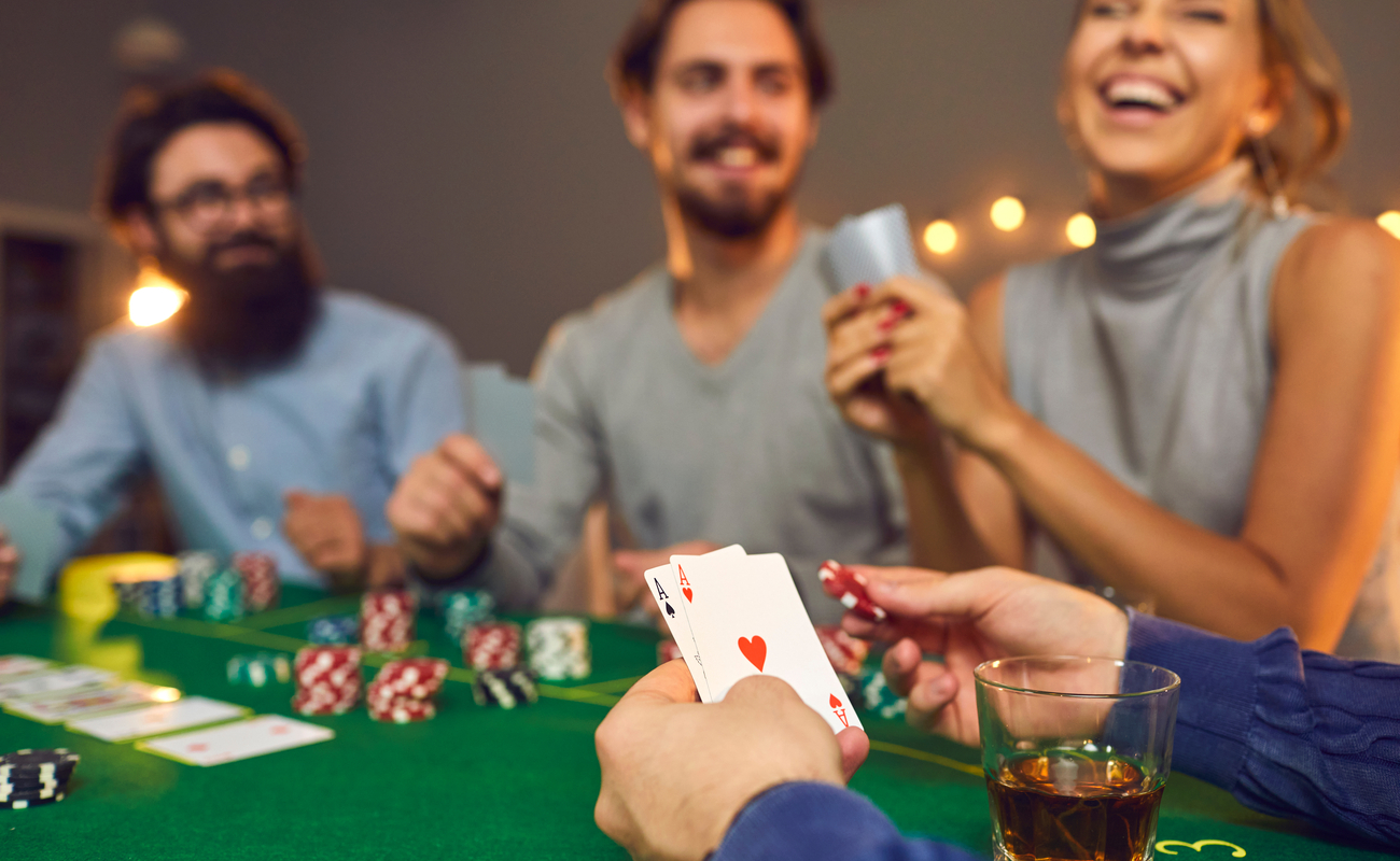 Friends enjoying a casino games party play cards at a felt-covered table.