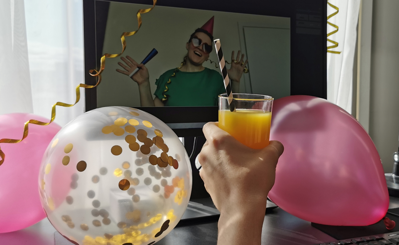 A virtual party with pink balloons in the foreground as a woman toasts a friend on her computer screen.