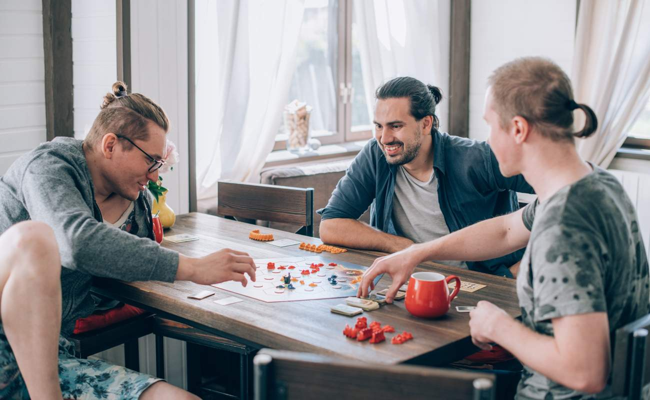 Three men playing a board game at the table.