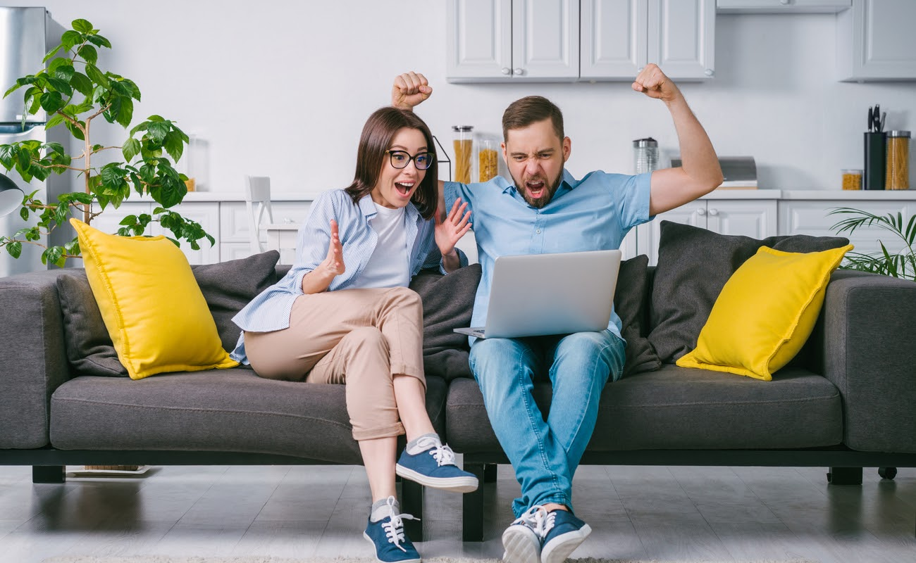 Excited couple playing online casino games on a laptop computer.