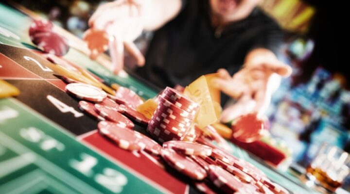 A pile of casino chips sit on top of a casino table.