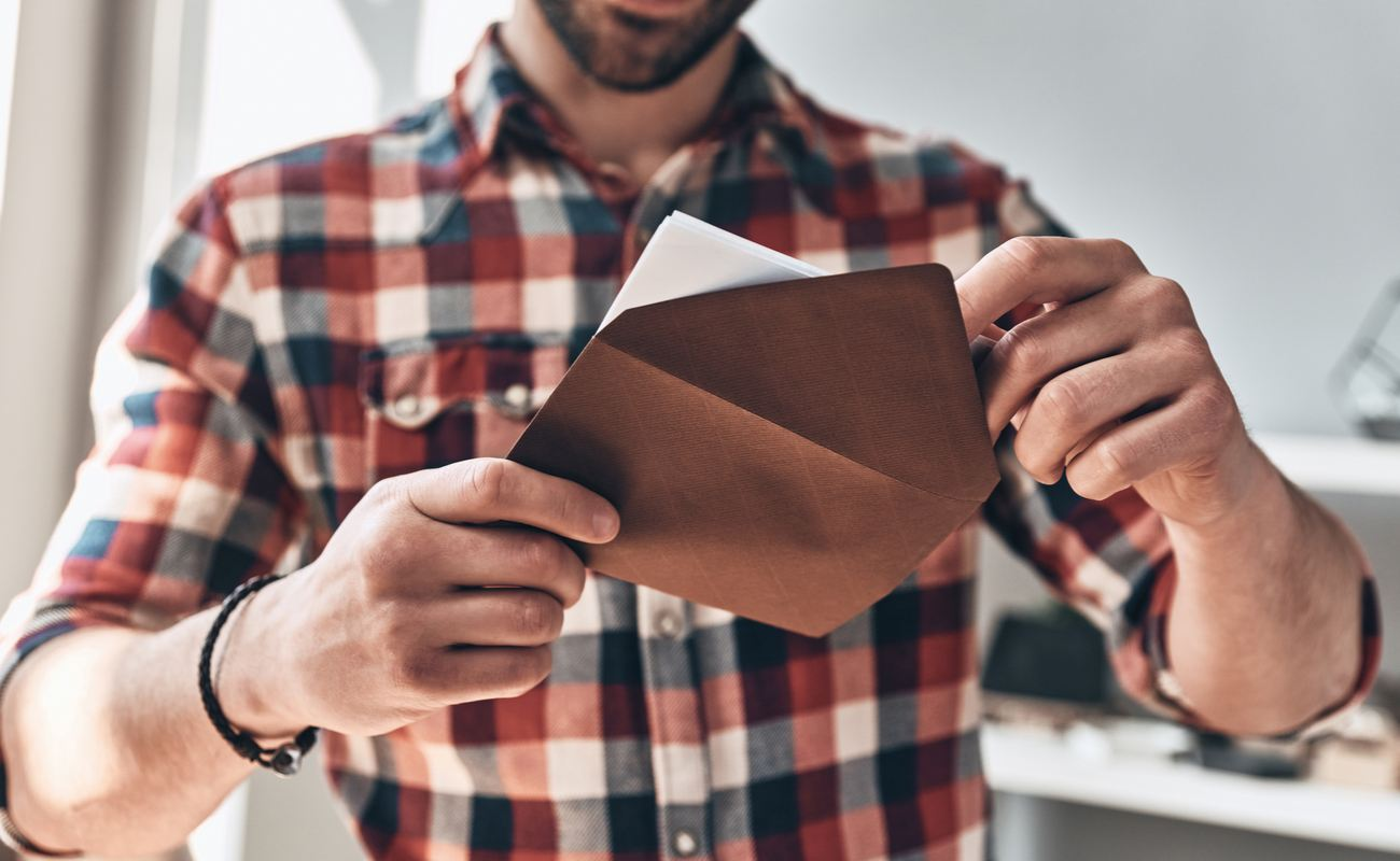 A man opens an envelope with a dinner party invitation.