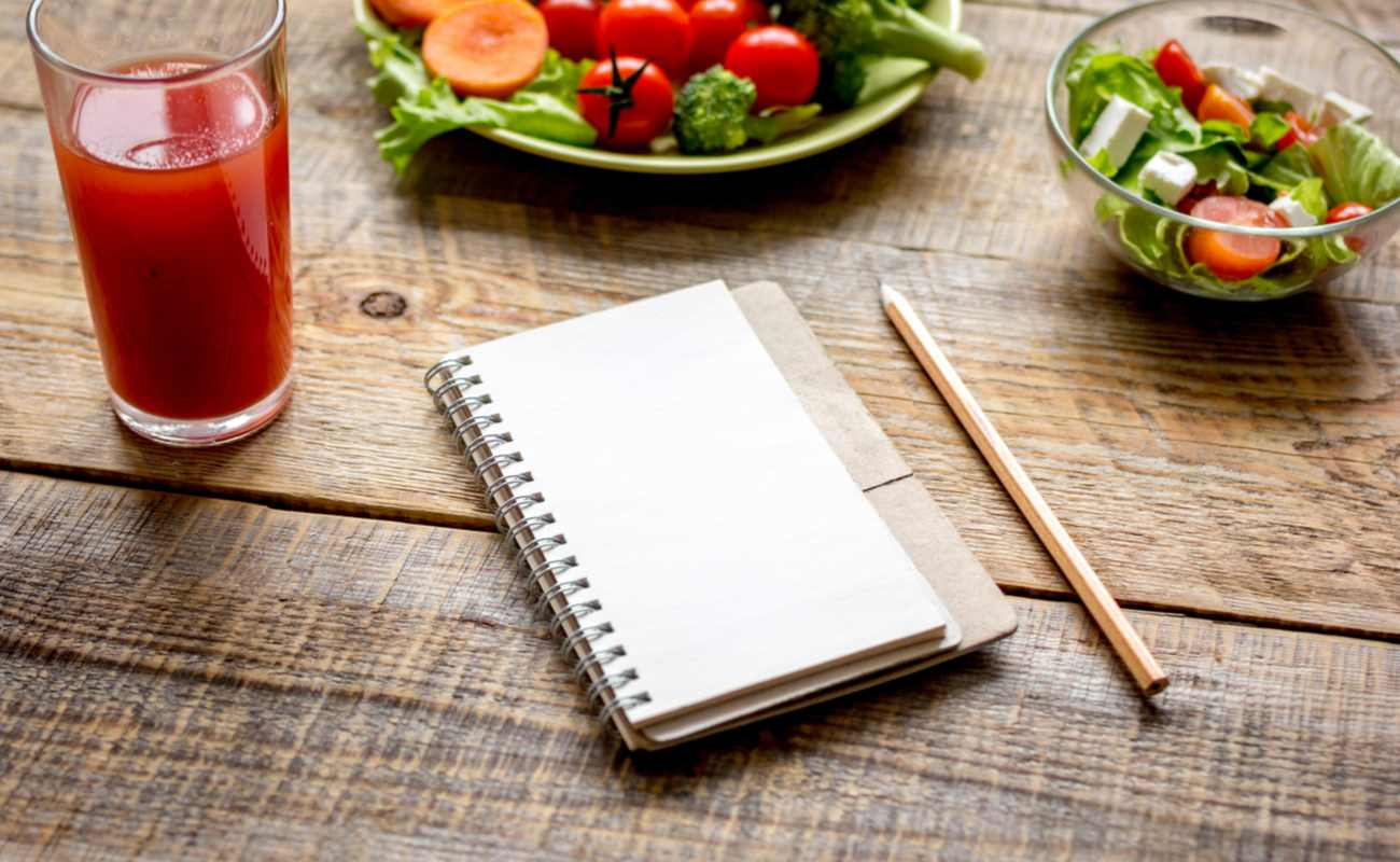 A notepad sits on a table next to a glass and some plates of food.
