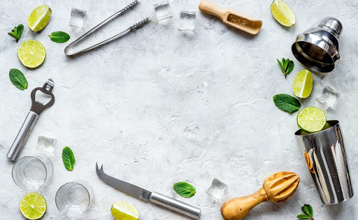 Cocktail-making tools displayed with mint leaves, ice, and lime slices.