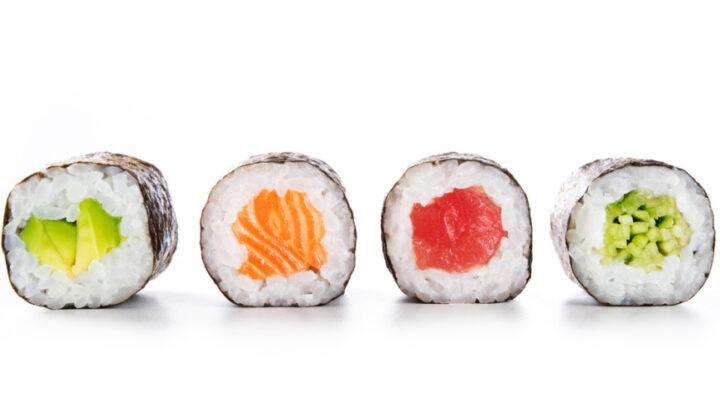 Four maki rolls with avocado, salmon, tuna, and cucumber.